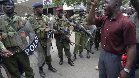 A supporter of Raila Odinga chants slogans on March 30 in front of police officers outside the Supreme Court in Nairobi, Kenya.