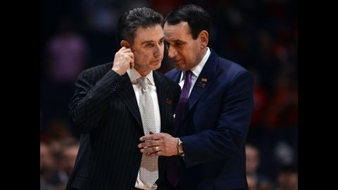 Duke head coach Mike Krzyzewski, right, shares a moment with Louisville head coach Rick Pitino as medical technicians take care of Ware.