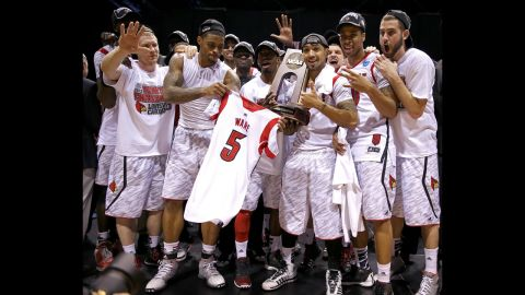 Ware's teammates hold his jersey with the Midwest regional champion trophy after they won 85-63 against Duke.