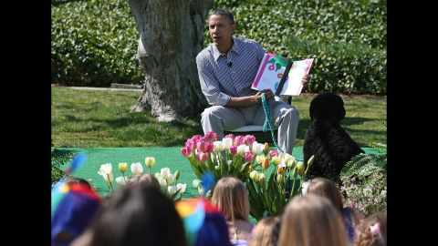 Obama sits with his dog Bo and reads a book to children.