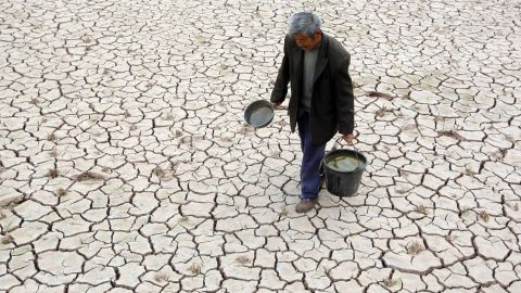 Villager Fu Xianxing, 70, walks on a dried-up field Tuesday, April 2, in Suining, China. A severe drought has caused a shortage of drinking water in the area in southwest China's Sichuan province.