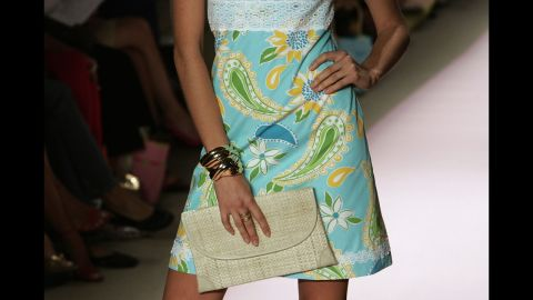 A model holds a clutch bag at the end of the runway at the 2005 show.