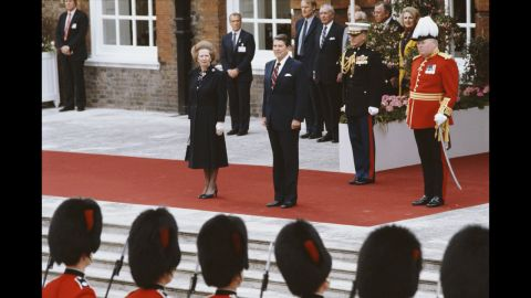 Thatcher and Reagan listen to the American national anthem at Kensington Palace Gardens after Reagan's arrival from Ireland for a summit in London in June 1984.