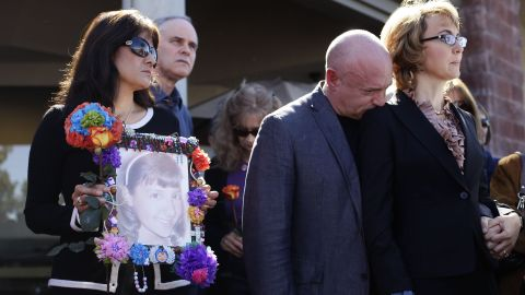 Giffords and Kelly attend a news conference on March 6, 2013 outside the Safeway grocery store in Tuscon. At the event they urged Congress to provide stricter gun control in the United States. At left, Roxanna Green holds a photo of her daughter, Christina Taylor Green, who was killed in the 2011 shooting.