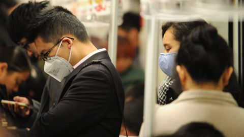 People wear masks to protect themselves from the H7N9 virus, or bird flu, while riding the underground in Shanghai on Tuesday, April 9.