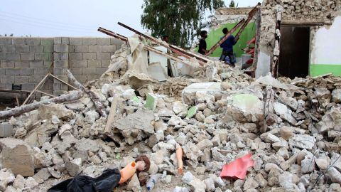People survey a destroyed house in the village southeast of the Persian Gulf port city of Bushehr.