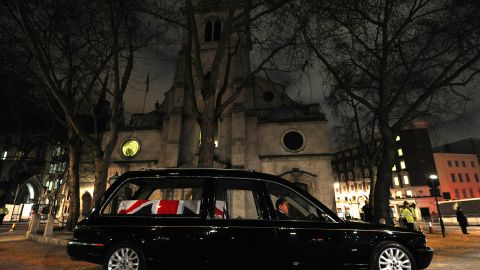 A hearse carrying a coffin waits outside St Clement Danes church.