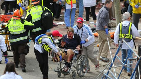 An injured person is taken away from the scene in a wheelchair.