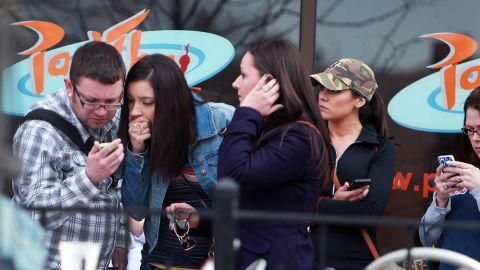 Bystanders check their mobile devices for news of the explosions.