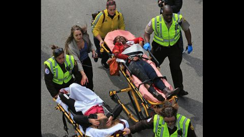 Two injured women are taken away on stretchers.
