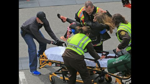 An injured woman is placed on a stretcher.