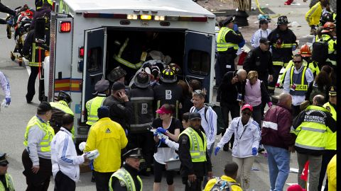 First responders load injured people into an ambulance.