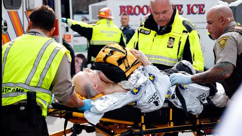 An injured man is prepared to be moved from a stretcher to an ambulance.