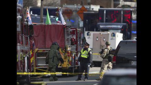 Bomb squad officials check a possible suspicious device near the scene of the blasts.