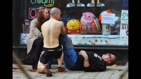 Passersby put pressure on a victim's leg to try to stop the bleeding.