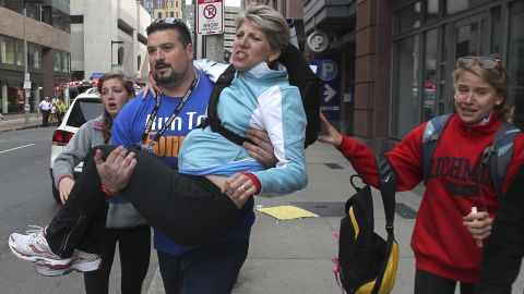 """Former New England Patriots <a href=""""http://bleacherreport.com/articles/1606043-former-new-england-patriot-joe-andruzzi-assists-survivors-at-boston-marathon"""" target=""""_blank"""" target=""""_blank"""">offensive lineman Joe Andruzzi</a> carries a woman from the scene."""
