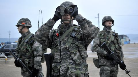 A South Korean soldier looks through binoculars as they patrol on the South Korea-controlled island of Yeonpyeong near the disputed waters of the Yellow Sea at dawn on April 14, 2013.