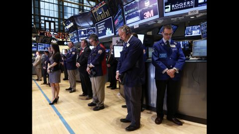 Traders at the New York Stock Exchange observe a moment of silence before the opening bell on April 16, 2013.