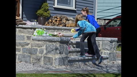 Two young girls leave flowers on the steps outside the Boston home of 8-year-old bombing victim Martin Richard on April 16, 2013.