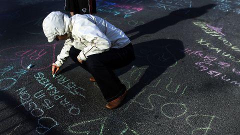 Danielle Cerroni writes a chalk message on the street near the marathon's finish line on April 17, 2013.