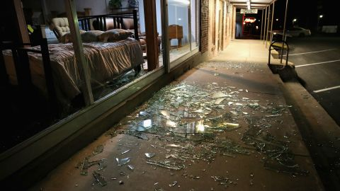 Glass from blown-out windows lies shattered on the sidewalk and street after the blast.