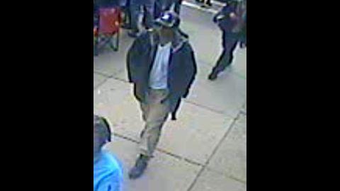 Suspect 1 walks through the crowd.