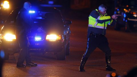 """Police officers keep a man on the ground in Watertown on Friday. <a href=""""http://www.cnn.com/2013/04/19/us/gallery/boston-ghost-town/index.html"""">See all photography related to the Boston bombings.</a>"""