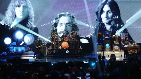 Alex Lifeson, Neil Peart, and Geddy Lee of Rush perform onstage.