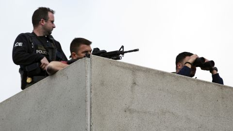 Law enforcement officers place themselves in an overhead position on Arsenal Street as the search continues on April 19.