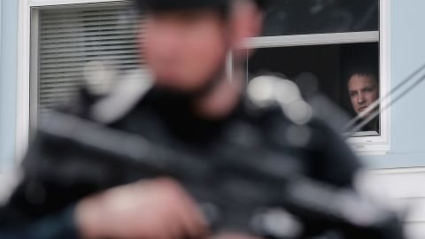 A man watches from the window of a home as a SWAT team member keeps watch on Friday, in Watertown, Massachusetts.