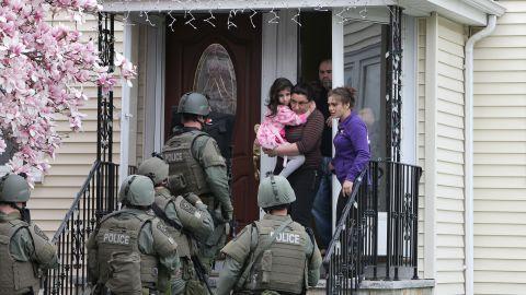 SWAT teams prepare to enter a home as they continue the door-to-door search.