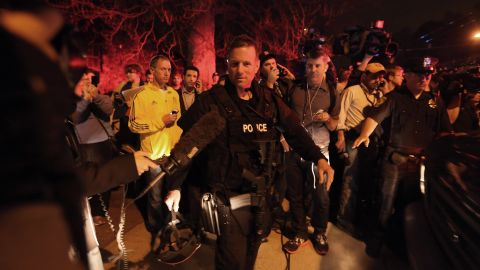 A SWAT team member is followed by reporters and a celebrating crowd  on April 19 after the successful operation.
