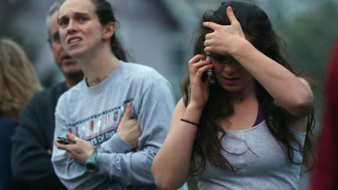 People react while watching police respond to reported gunfire on April 19.