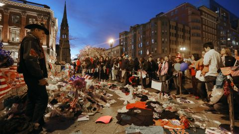 BOSTON, MA - APRIL 20: People gather at a makeshift memorial for victims near the site of the Boston Marathon bombings a day after the second suspect was captured on April 20, 2013 in Boston, Massachusetts.
