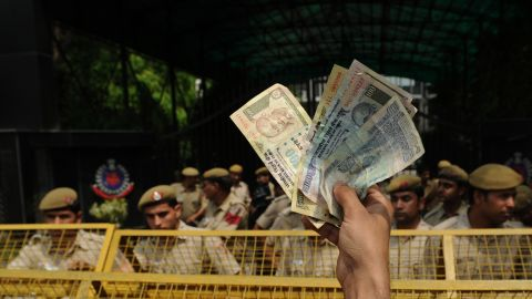 An Indian protester waves Indian currency toward police at a demonstration on April 21. Protests have swept through New Delhi since Friday. Many demonstrators are members of a political party of Arvind Kejriwal, a leading anti-corruption activist.