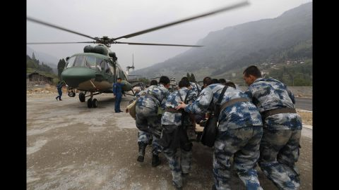 Rescuers evacuate an injured survivor onto a military helicopter on Sunday.