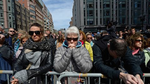 People take part in the moment of silence near the marathon finish line.