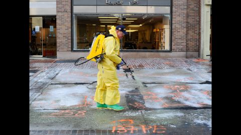 A member of the Boston Fire Department Hazardous Materials team cleans the first blast site with a pressure washer on April 22.