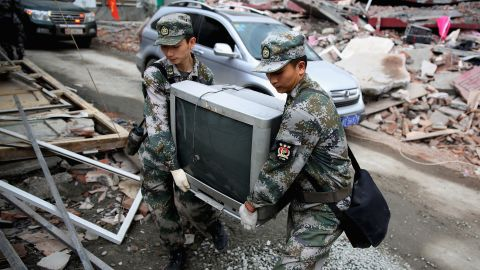 Two soldiers help move a television from a damaged house on Monday in Ya'an.