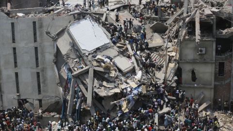 People rescue garment workers on Wednesday, April 24, after the building caved in, leaving a chaotic mass of broken concrete and twisted metal.<br />