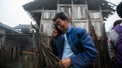 A man wipes away tears in front of a damaged house on Tuesday.