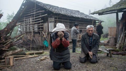 A man and woman react to the damage in Ya'an on Tuesday.