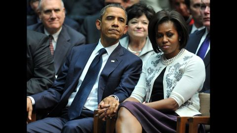 The President and first lady hold hands during a memorial service for the victims of a Tucson, Arizona, shooting. On January 8, 2011, Jared Lee Loughner shot six people and wounded 13 more, including then-Rep. Gabrielle Giffords.
