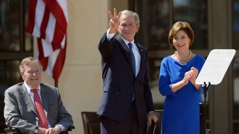 """George W. Bush gestures a """"W"""" to the crowd after speaking."""