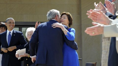 George W. Bush hugs his wife Laura after speaking.
