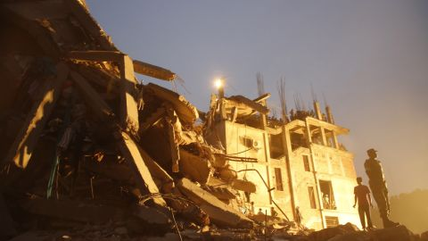 Rescue workers stand on the rubble of the collapsed building on April 26.
