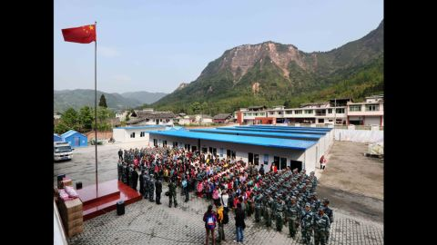 Students and soldiers from the air force attend a flag-raising ceremony in Baosheng Primary School in Lushan County, southwest China's Sichuan province, April 26. The primary school was built within 28 hours by the air force troops from the People's Liberation Army Chengdu Military Area Command, who also donated stationery and computers to students and teachers affected by the earthquake.