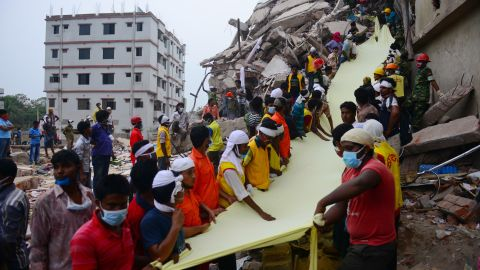 Rescue workers use textile as a slide to move bodies out of the rubble on April 26.