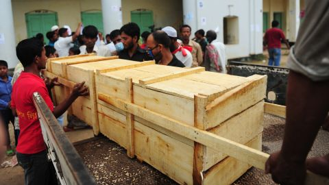 Bangladeshi relatives and workers load a body onto a truck on April 27.