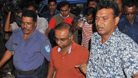 An arrested owner of a garment factory is escorted to an appearance at the court in Dhaka on April 27. Four people were arrested and four others are being questioned by police.